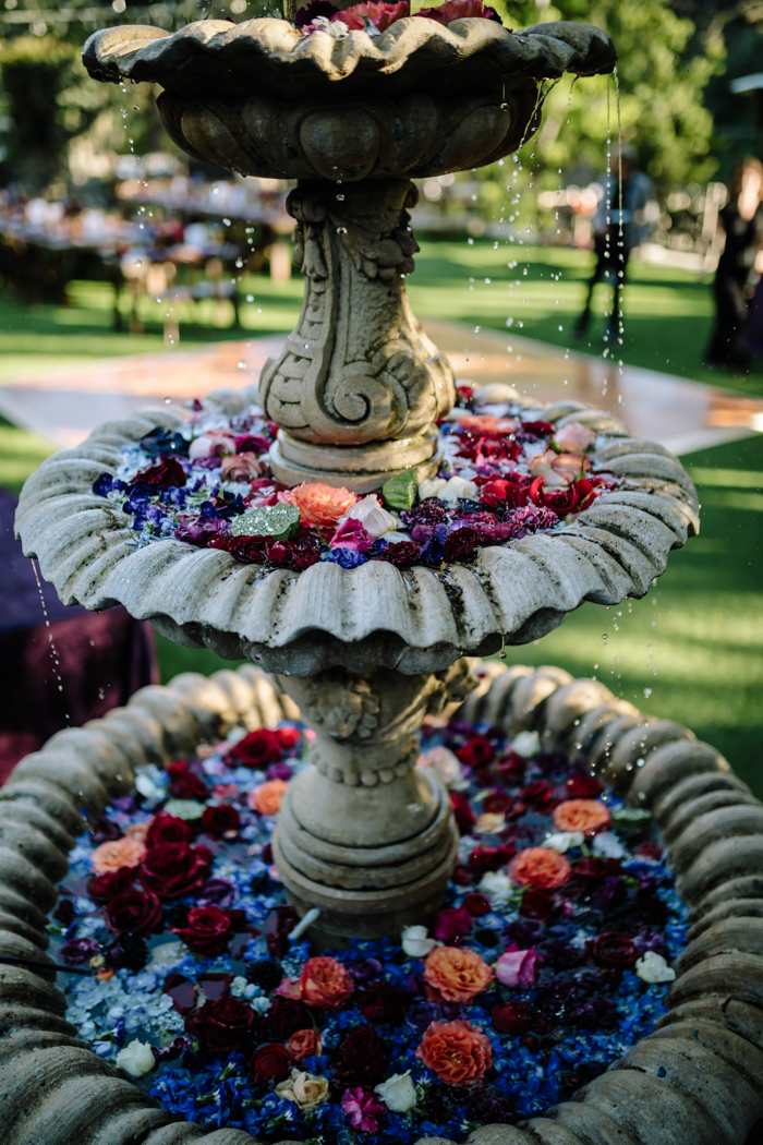 Houdini Estate's water fountain decorated with moody jewel toned petals and buds by Winston and Main.