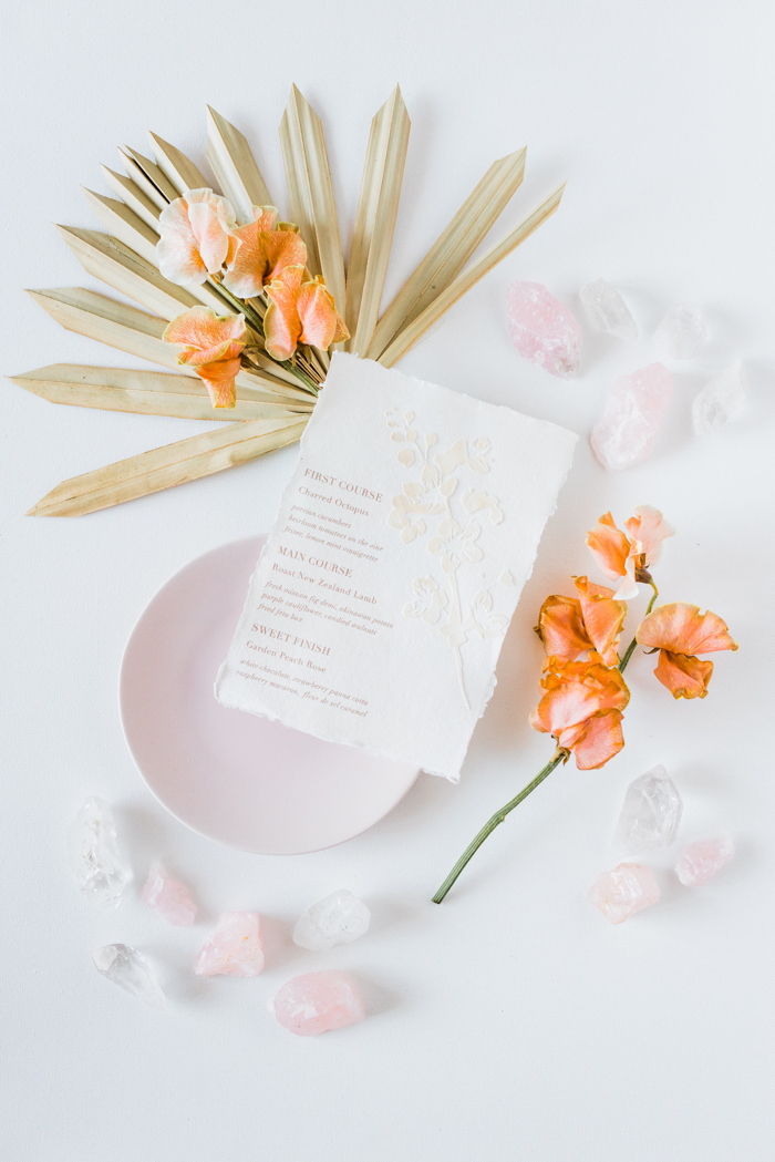 Custom paper wedding invitations by Cecile Paper surrounded by Winston and Main flowers