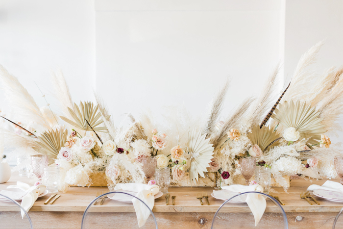 Textured natural and dry flower arrangements featuring pampas and sun palms on a farm table.