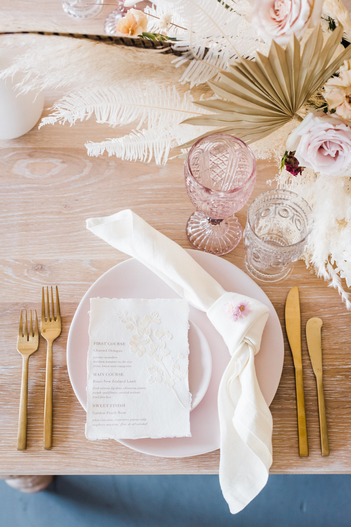 A wedding reception table featuring gold flatware, blush tableware, and dried natural flower arrangements