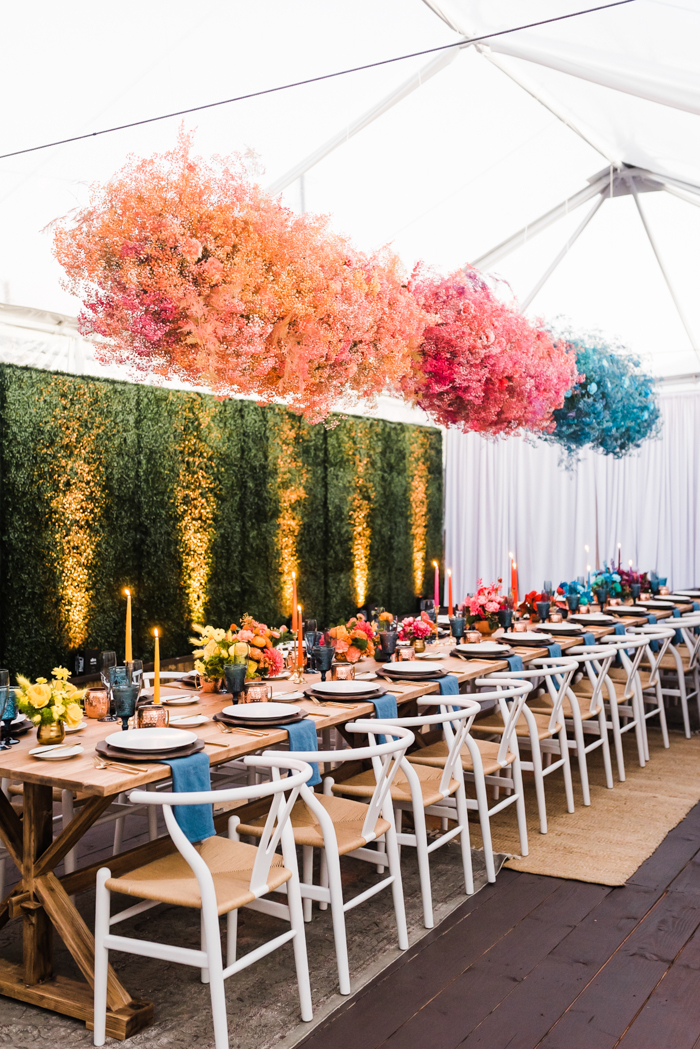 Bright and bold dyed babies breath clouds by Winston & Main hang over long table at colorful LA birthday celebration.