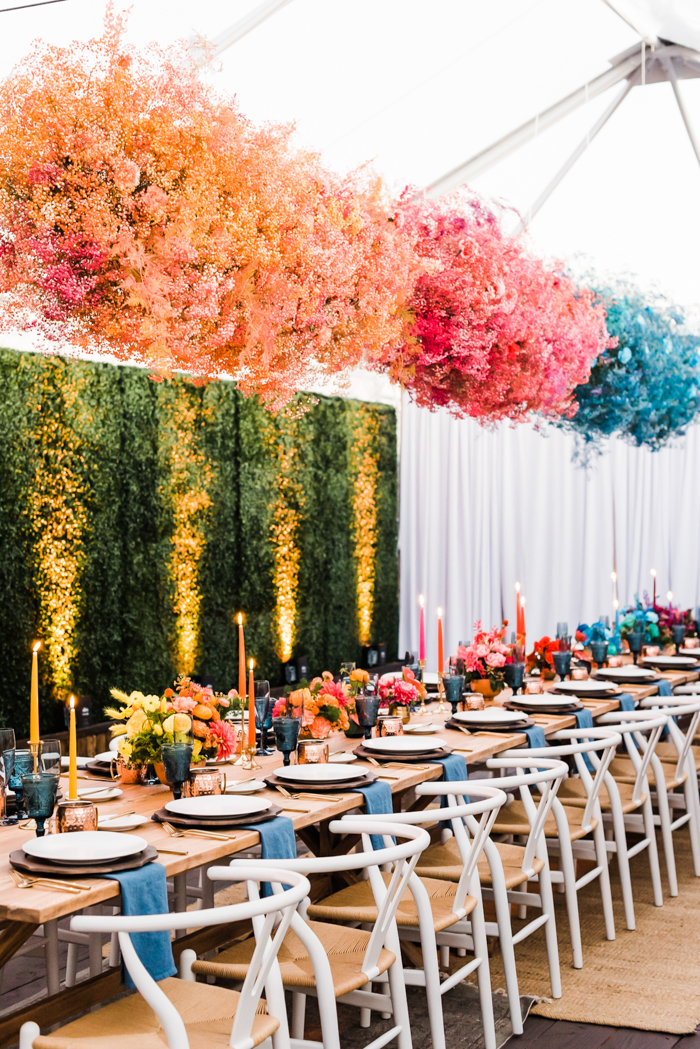 Bright and foam free floral clouds of dyed baby's breathe hanging over table of ombre floral arrangements.