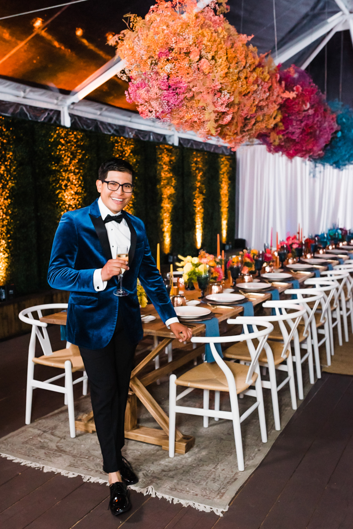 The guest of honor wears a luxe blue velvet dinner jacket and is standing under 21 feet of bold and colorful floral clouds.