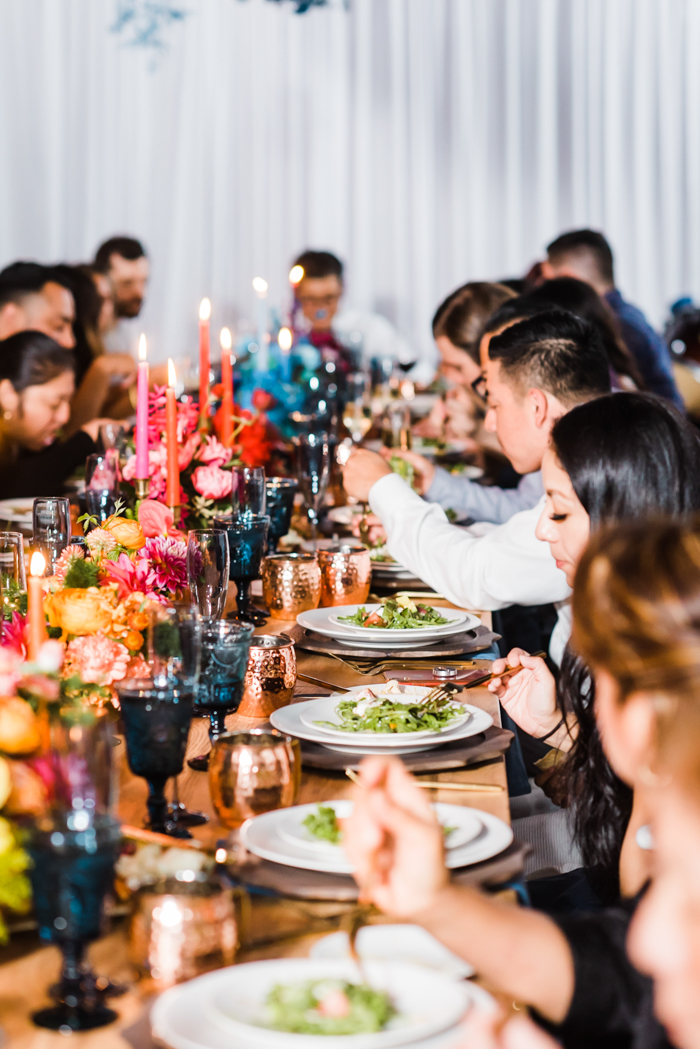 A wildly colorful dinner party with brightly colored ombre candles and florals down the length of the table.