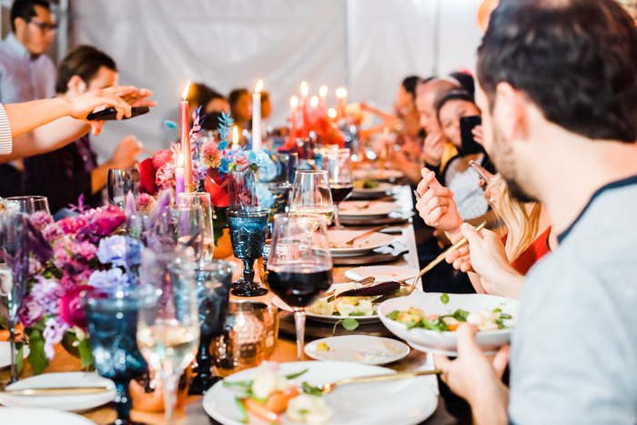 A long table of guests enjoying a warm, colorful, and festive intimate birthday party.