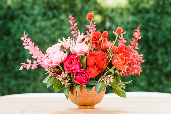 Bold pink and red floral arrangement featuring double tulips, clover, dahlias, and painted italian ruscus by Winston & Main