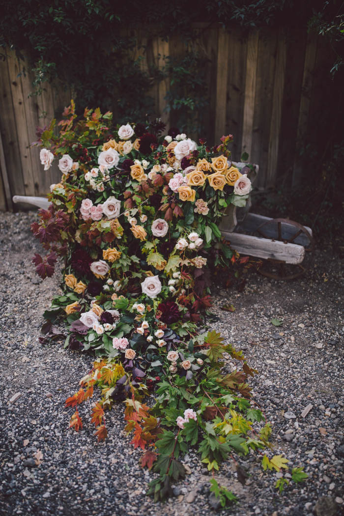 Lush and elegant fall flowers and foliage cascading from a vintage wheelbarrow.