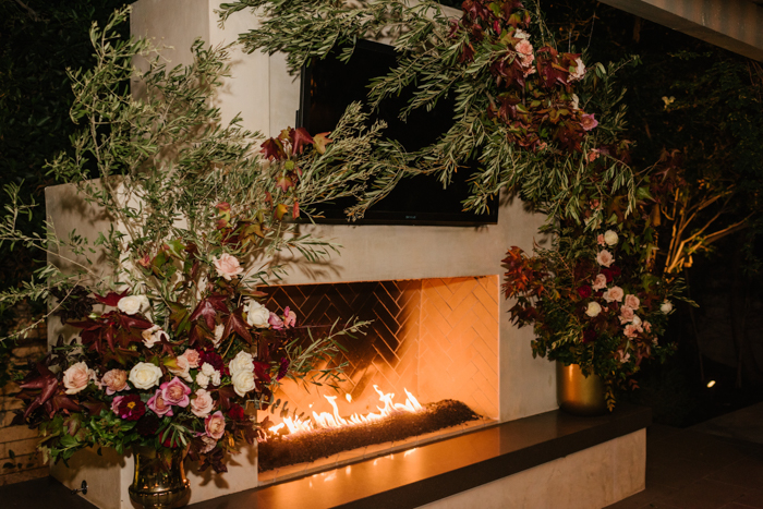 Fall floral installation, foam free, surrounding elegant outdoor fireplace.