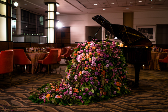 Piano with lush foam free floral installation spilling onto floor.