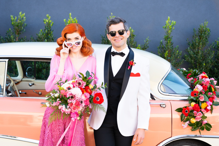 A colorful Valentine's Day wedding couple pose with their vintage pink car.