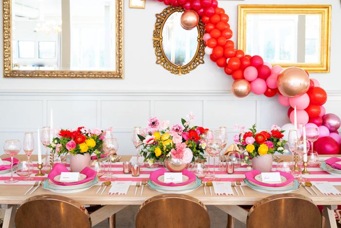 A brilliant Valentine's Day tablescape featuring pink Japanese ranunculus and red anemones with a balloon garland backdrop.