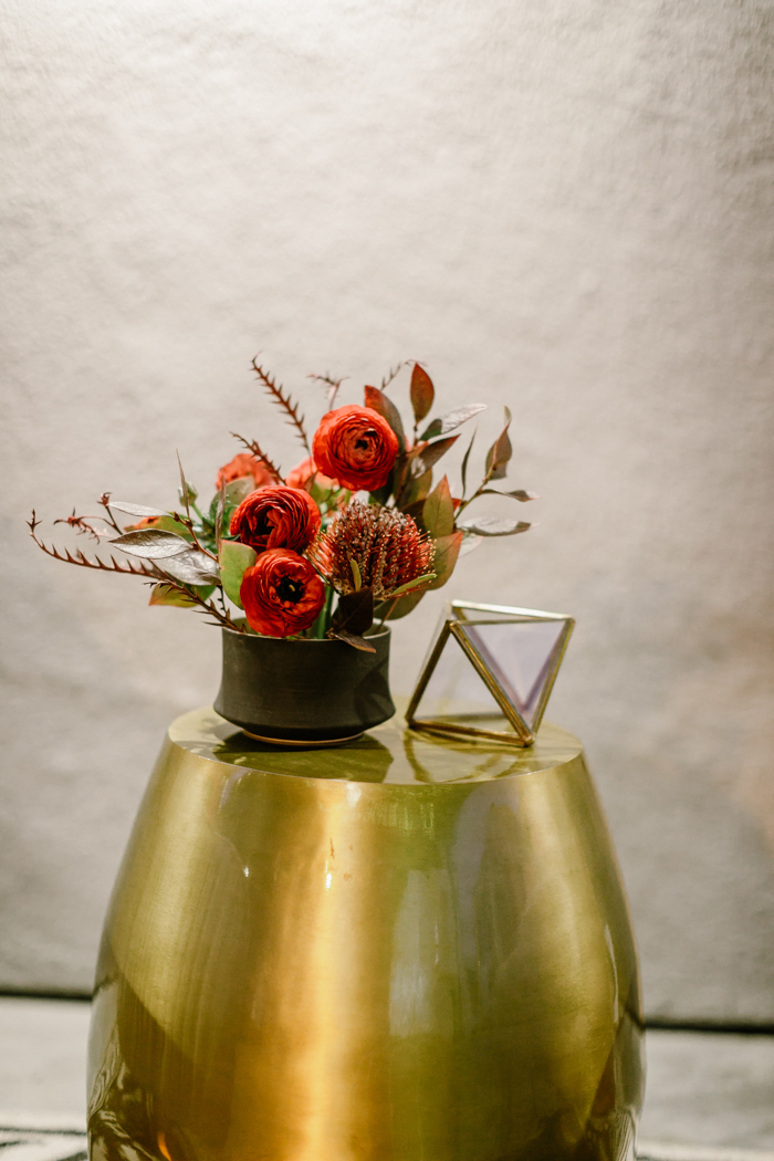 A bold & textural tomato red cocktail arrangement featuring ranunculus, and banksia.