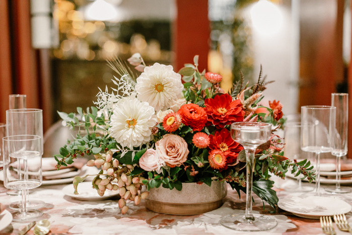 Beautiful red ombre centerpiece featuring dahlias, ranunculus, cappuccino roses, and strawflower by Winston & Main