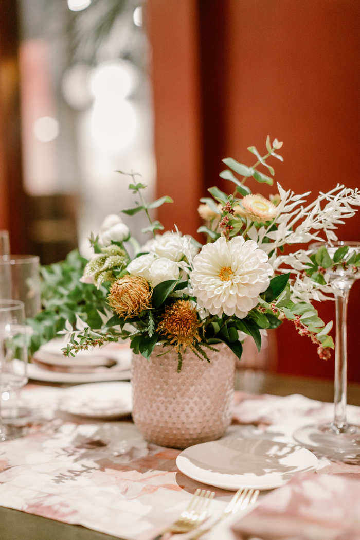 An organic floral arrangement featuring white dahlias, strawflowers, and banksia by Tabitha Abercrombie of Winston & Main.