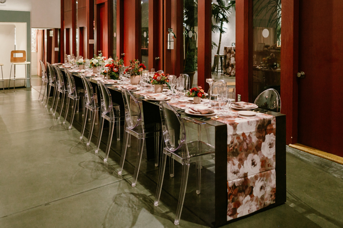 Long & dramatic tablescape featuring floral runner, and ombre red floral arrangements by Winston & Main.