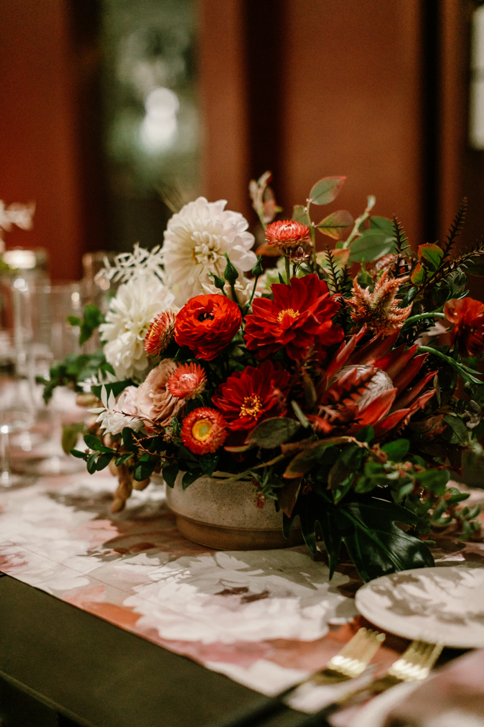 Lush centerpiece featuring King Protea, Ranunculus, Strawflowers, Dahlias, and more in shades of red, mauve, and white.