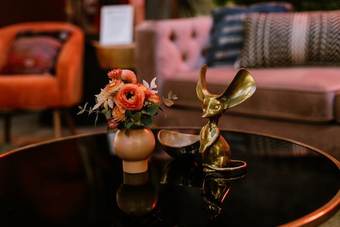 A petite red floral arrangement, perfect for a cocktail hour, sits on a coffee table with a brass mouse statue.