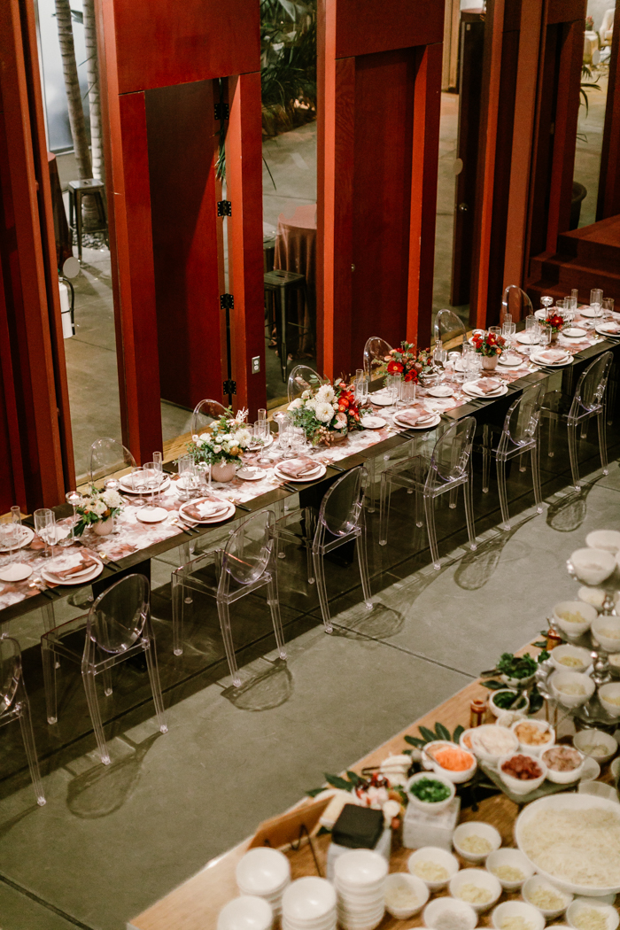 A birds-eye-view of a long ombre tablescape, and a ramen bar at Kim Sing Theatre.