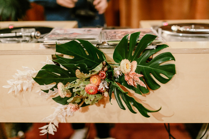 Floral Decor on DJ Booth created from monstera leaves and dried floral elements.