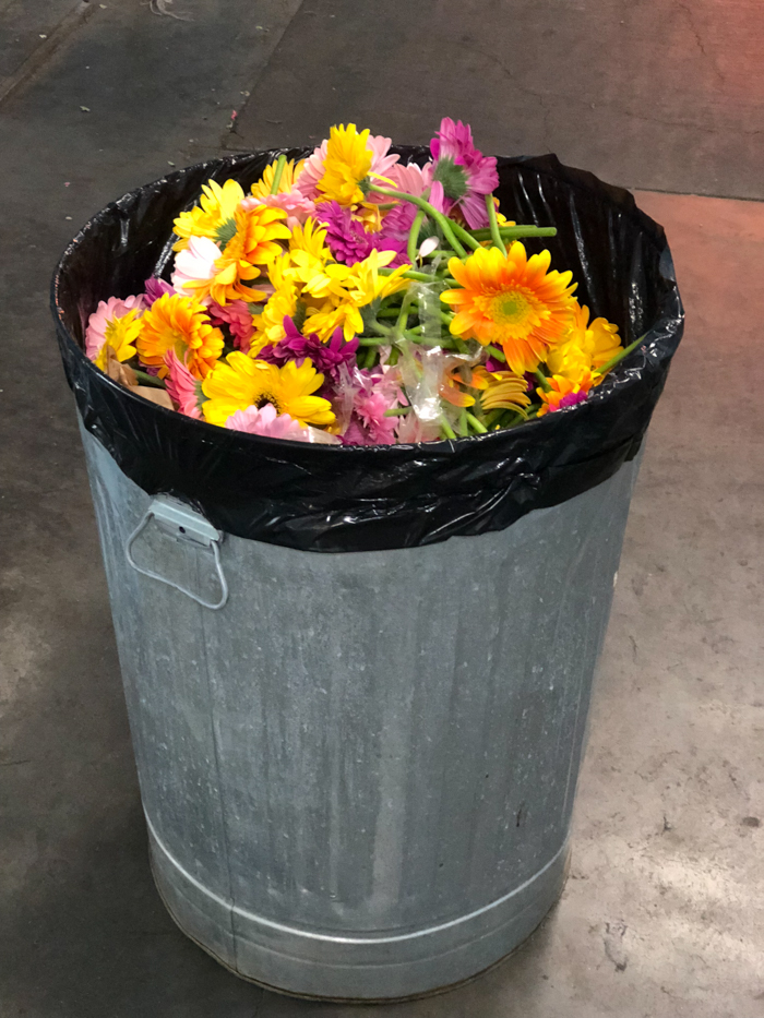 A trash can full of brightly colored flowers, following an event.