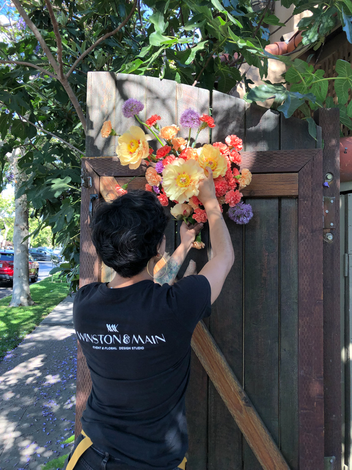 A Winston & Main team member finished a foam-free floral installation on a gate for a recent wedding.