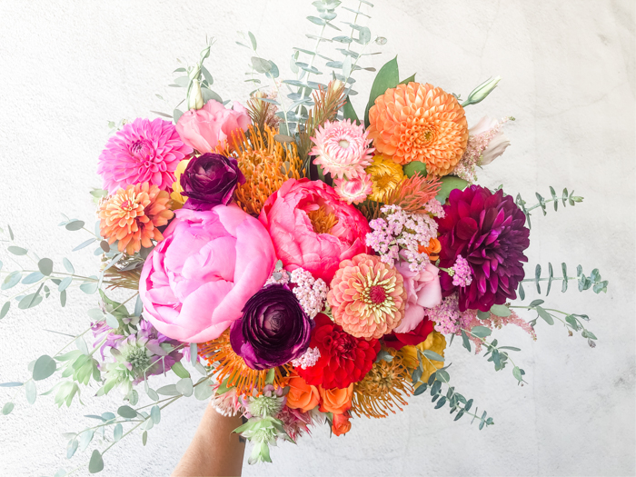 A bright & bold bouquet by Winston & Main featuring peony, dahlia, ranunculus, and zinnia for a 2020 elopement.